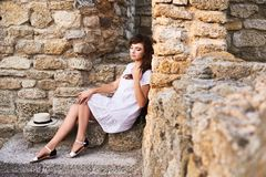 Thoughtful peasant girl sitting on the steps and holding her hair royalty free stock photo