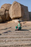The girl is sitting on the steps. The girl sits on the stone steps carved into the rock, in the background huge stones Stock Image