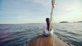 Girl sitting on the stern of the yacht. Happy Traveling in the Sea. A young lady girl woman with long brown hair sitting. Girl sitting on the stern of the yacht stock video