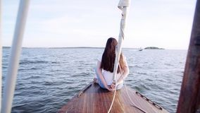 Girl sitting on the stern of the yacht. Happy Traveling in the Sea. A young lady girl woman with long brown hair sitting. Girl sitting on the stern of the yacht stock footage