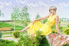 The girl is sitting on a stone Royalty Free Stock Images