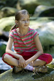 Girl sitting on a stone Stock Photography