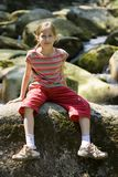 Girl sitting on a stone Royalty Free Stock Photo