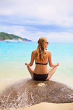 Girl sitting on stone backward near sea. Blonde woman wearing swimsuit sitting on big stone backward in lotus pose near blue sea outdoor focus on water drops Stock Photo