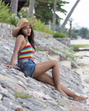 Girl sitting on a stone causeway. Young woman sitting on the shore Royalty Free Stock Photo
