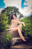 The girl sitting on the stone. The embodiment of femininity Royalty Free Stock Image