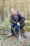 Girl sitting on the stone. In the forest Stock Photo