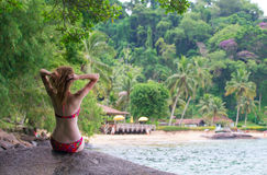 Girl sitting on a stone. And looking at the small brazilian beach Royalty Free Stock Photo