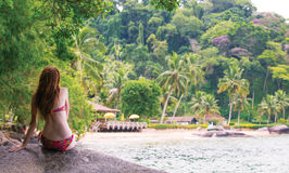 Girl sitting on a stone. And looking at the small brazilian beach Stock Images