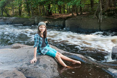Girl sitting on a stone near the Strong Falls, Wisconsin, USA. Smiling girl sitting on a stone near the Strong Falls in the Goodman park, Marinette County Stock Photo