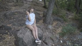 Girl sitting on a stone by the river. A girl sits on a large stone under the trees by the river stock video footage