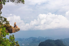 Girl sitting at the stone rock. Picturesque observation point Stock Photo