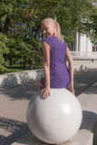 Girl sitting on a stone sphere Stock Photo