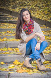 Girl sitting on stone steps. In autumn Park Royalty Free Stock Images