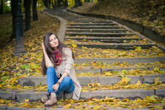 Girl sitting on stone steps. In autumn Park Royalty Free Stock Photography