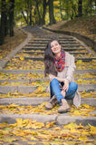 Girl sitting on stone steps. In autumn Park Royalty Free Stock Photo