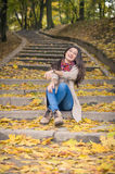 Girl sitting on stone steps. In autumn Park Stock Image