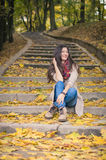 Girl sitting on stone steps. In autumn Park Stock Photography