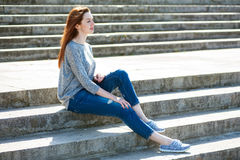 Girl sitting on stone steps 01. Beautiful young girl sitting on stone steps Royalty Free Stock Image