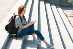 Girl sitting on stone steps 04. Beautiful young girl sitting on stone steps with telephone and backpack Stock Photo