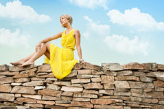 The girl is sitting on a stone wall Stock Photography