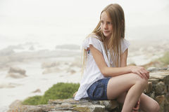 Girl Sitting On Stone Wall Royalty Free Stock Images