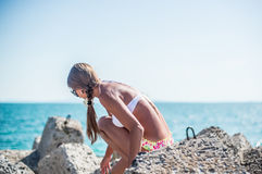 Girl sitting on the stones at the beach Stock Photography