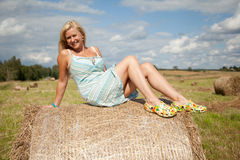 Girl sitting on the straw bale Royalty Free Stock Photos