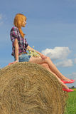 Girl sitting on straw bale Royalty Free Stock Photos