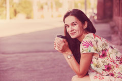 Girl sitting in street with coffee Stock Image