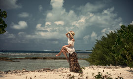 A girl is sitting on a stump in a white dress and hat. The shore of the ocean. Maldives. Tropics. Vacation. Island. Stock Photos