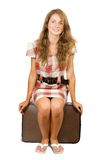 Girl sitting on suitcase Royalty Free Stock Image