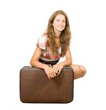 Girl sitting with suitcase Stock Photography