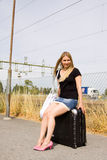 Girl sitting on a suitcase. Waitin for the train or bus Royalty Free Stock Photo