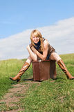 Girl sitting on the suitcase. Pretty blond girl wearing leathern boots sitting on the suitcase on the road royalty free stock photo