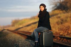 Girl sitting on a suitcase. Along the train tracks royalty free stock photography