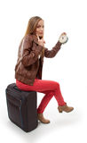 Girl sitting on suitcase with clock, flight delay Royalty Free Stock Images