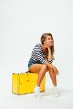Girl sitting on a suitcase Royalty Free Stock Images