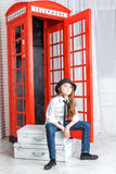 Girl sitting on a suitcase near the phone booth Royalty Free Stock Photography