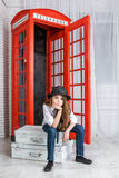 Girl sitting on a suitcase near the phone booth Stock Image