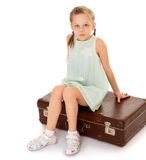 Girl sitting on suitcase Stock Image