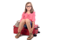 Girl sitting on a suitcase Stock Images