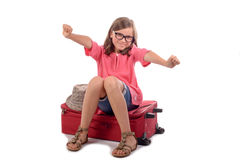 Girl sitting on a suitcase Royalty Free Stock Photos