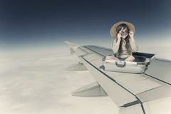 Girl sitting in the suitcase on the wing of the plane in flight Stock Photos