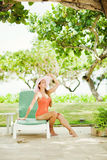 Girl sitting on sunbed near the tree Stock Photography
