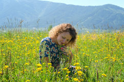 Girl sitting on the Sunny meadow Royalty Free Stock Photography