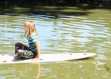Girl sitting on surf. Barefoot girl in wet clothes sitting and playing on surf board in water of pond Royalty Free Stock Photography