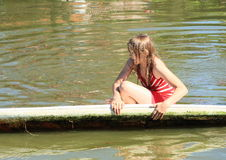 Girl sitting on surf. Blond girl in wet clothes sitting and playing on surf board in water of pond Stock Photos