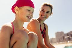 Smiling child with swimming coach. Girl sitting on swimming pool edge with her trainer. Smiling child with swimming coach royalty free stock image
