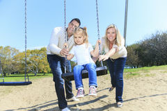 Girl sitting on a swing, father on mother pushing Stock Photos